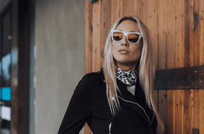 A pretty blonde woman looking into the distance wearing sunglasses