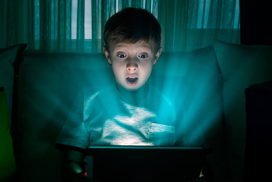 A young boy gasping at his tablet device