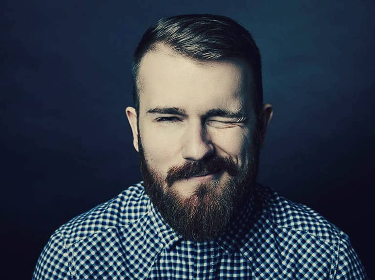 A young bearded man that is smiling and winking