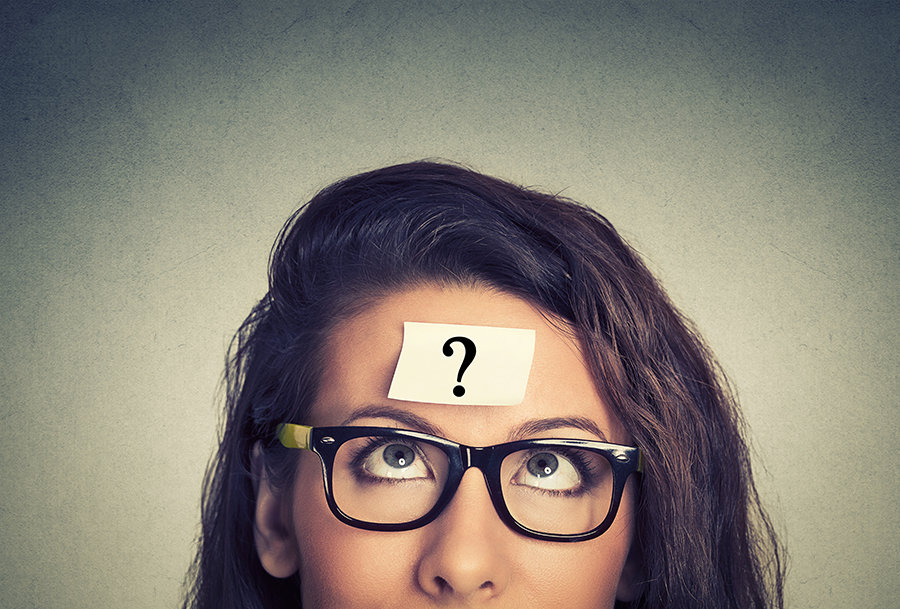 A confused looking woman wearing glasses with a question mark on her forehead