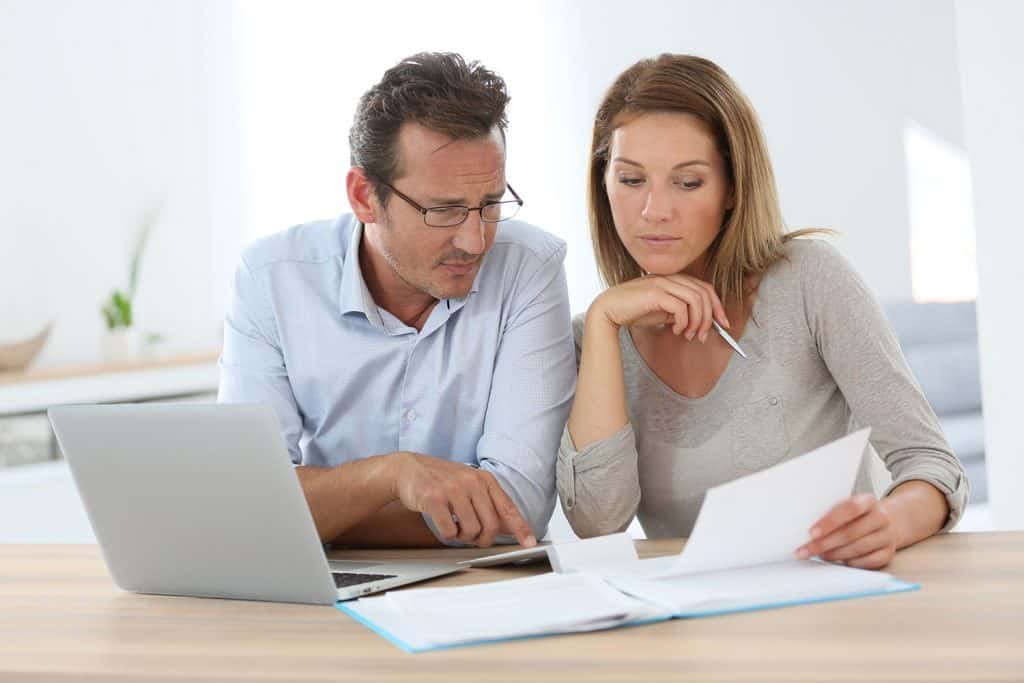 A concerned couple looking at some paper work